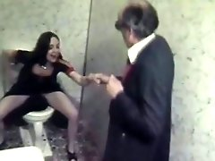 A girl and an elderly man walk into a bathroom where she sits down on...