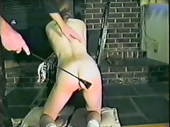 Brown-haired girl gets her ass spanked in the garage in vintage clip